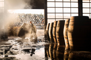Male cooper working in cooperage with whisky casksの写真素材 [FYI03520819]