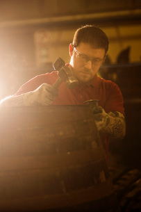 Male cooper using hammer in cooperage with whisky caskの写真素材 [FYI03520821]