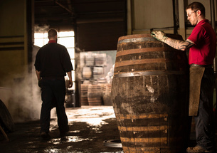 Male cooper working in cooperage with whisky caskの写真素材 [FYI03520822]
