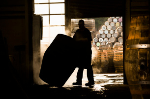 Silhouette of man working in cooperage with whisky caskの写真素材 [FYI03520824]