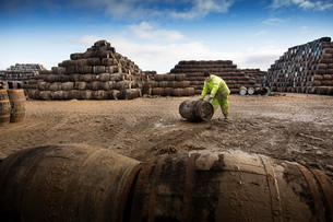Young man rolling whisky cask at cooperageの写真素材 [FYI03520850]