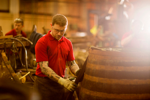 Mid adult man making whisky cask at cooperageの写真素材 [FYI03520854]