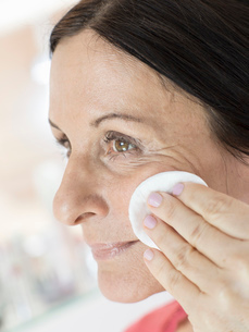 Mature woman removing make up from face with cotton padの写真素材 [FYI03520921]