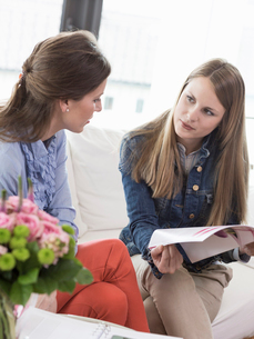 Young businesswoman interviewing mid adult woman on living room  on sofaの写真素材 [FYI03520928]