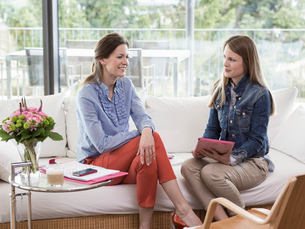 Young businesswoman interviewing mid adult woman on sofaの写真素材 [FYI03520930]