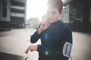 Young male runner checking neck pulse in city squareの写真素材 [FYI03521012]