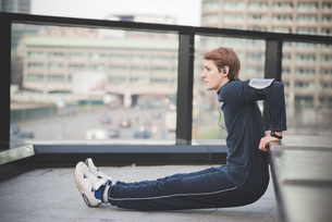 Young man doing reverse push ups on city rooftopの写真素材 [FYI03521034]