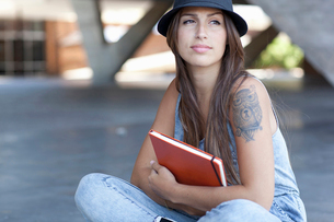 Female student with tattoo holding bookの写真素材 [FYI03521135]