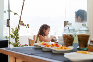 Father and daughter sitting at breakfast table on balcony, healthy food in foregroundの写真素材 [FYI03521282]