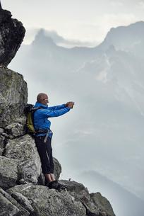 Mature man on rocks taking photo, Valais, Switzerlandの写真素材 [FYI03521352]