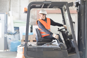 Young male warehouse worker reversing forklift truck in warehouseの写真素材 [FYI03521868]