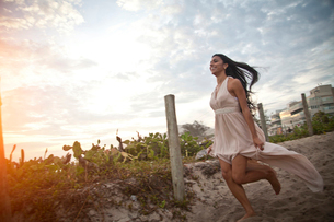 Mid adult woman running along sandy walkway towards beachの写真素材 [FYI03522062]