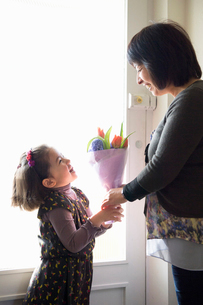 Young girl giving mother flowersの写真素材 [FYI03522228]
