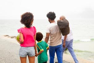 Rear view of family of four strolling along Ipanema beach, Rio De Janeiro, Brazilの写真素材 [FYI03522336]