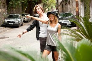 Young couple hailing a taxi on street, Rio De Janeiro, Brazilの写真素材 [FYI03522341]