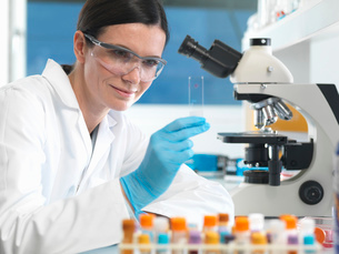 Scientist holding microscope slide with blood sample in labの写真素材 [FYI03522493]
