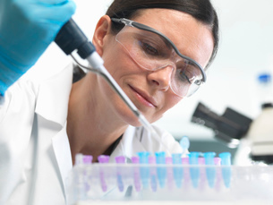 Scientist pipetting DNA sample into vial in labの写真素材 [FYI03522495]