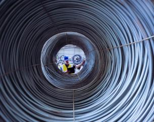 Worker inspecting rolls of steel wire in portの写真素材 [FYI03522509]