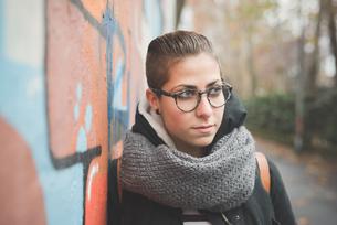 Teenager leaning against graffiti wallの写真素材 [FYI03522541]