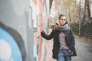Teenager leaning against graffiti wallの写真素材 [FYI03522542]
