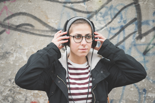 Teenager with headphones by graffiti wallの写真素材 [FYI03522555]