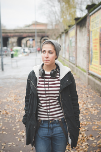 Teenager with headphones on streetの写真素材 [FYI03522556]