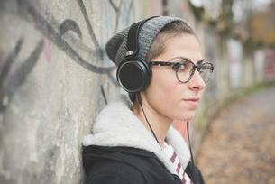 Teenager with headphones by graffiti wallの写真素材 [FYI03522557]