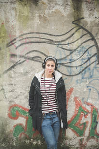 Teenager with headphones by graffiti wallの写真素材 [FYI03522558]