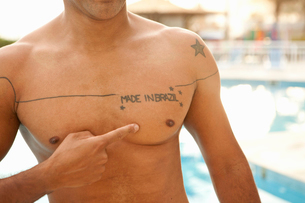 Cropped shot of man pointing to chest tattoo at hotel swimming pool, Rio De Janeiro, Brazilの写真素材 [FYI03522830]