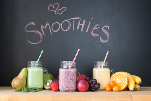 Still life of three fresh smoothies in front of blackboardの写真素材 [FYI03522890]