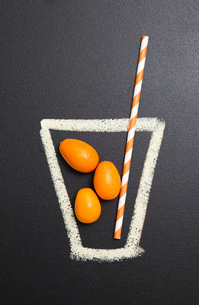 Blackboard illustration of drinking glass with kumquats and drinking strawのイラスト素材 [FYI03522891]