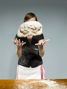 Studio portrait of young woman throwing bread dough mid airの写真素材 [FYI03522980]