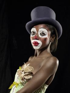 Studio portrait of young woman in clown face paint wearing top hatの写真素材 [FYI03522985]