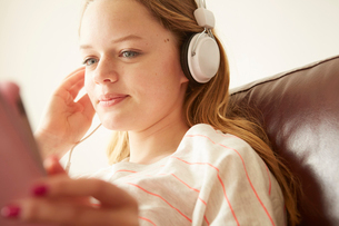 Close up of girl on sofa listening to music on headphonesの写真素材 [FYI03523188]