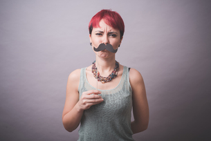Studio portrait of confused young woman holding up mustache in front of faceの写真素材 [FYI03523260]