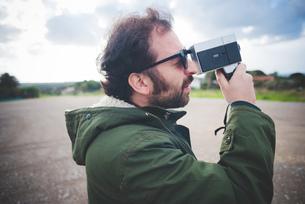 Mid adult man using vintage movie camera on waste groundの写真素材 [FYI03523293]