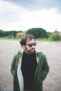 Mid adult man wearing sunglasses looking sideways on waste groundの写真素材 [FYI03523296]