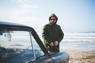 Mid adult man with vintage car fastening anorak on beach, Sorso, Sassari, Sardinia, Italyの写真素材 [FYI03523297]