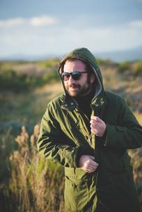Mid adult man fastening anorak at coast, Sorso, Sassari, Sardinia, Italyの写真素材 [FYI03523327]