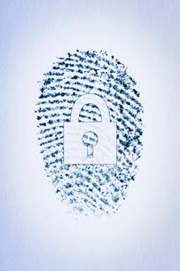 Lock outline over a fingerprint of a male's index fingerの写真素材 [FYI03523386]