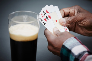 Man holding four ace cards with beerの写真素材 [FYI03523390]