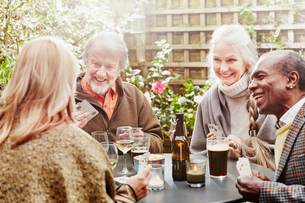 Senior friends drinking and playing cards in gardenの写真素材 [FYI03523410]