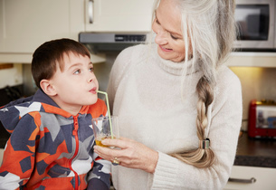 Grandmother offering grandson drinkの写真素材 [FYI03523439]