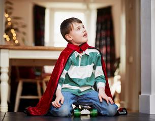 Young boy sitting on skateboard wearing capeの写真素材 [FYI03523452]