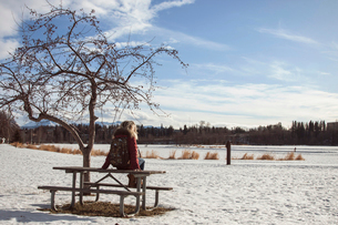 Young woman sitting on picnic bench, Anchorage, Alaskaの写真素材 [FYI03523499]