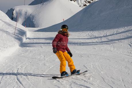 Young woman snowboarding, Girdwood, Anchorage, Alaskaの写真素材 [FYI03523504]