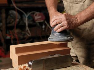 Boat builder sanding wood in workshopの写真素材 [FYI03523548]