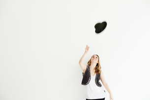 Mid adult woman throwing hat in the air, copy spaceの写真素材 [FYI03523566]