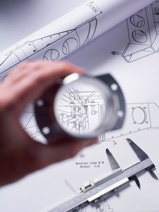 Engineer holding a precision made component over a technical drawing with a dial caliperの写真素材 [FYI03523802]