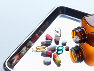 Close up of variety of medical drugs pouring from pill bottle on surgical trayの写真素材 [FYI03523833]